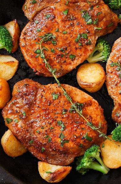 Vepřové kořeněné plátky s brokolicí a bramborami posypané bylinkami.