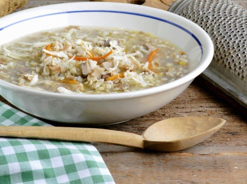 Vepřová polévka se zeleninou a kroupami v bílé misce.