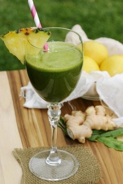 Zelená pampelišková šťáva ve sklenici na víno, zdobená kouskem ananasu a podávaná s brčkem.