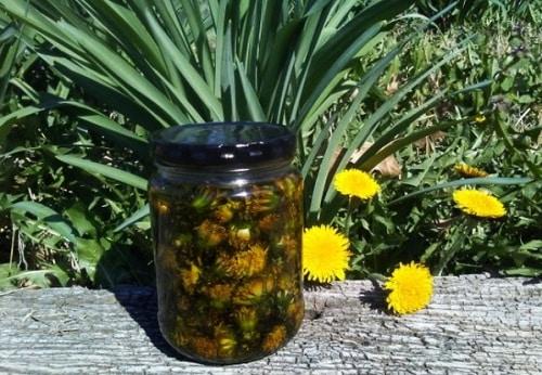 Olej s květy pampelišky ve sklenici s černým víkem.