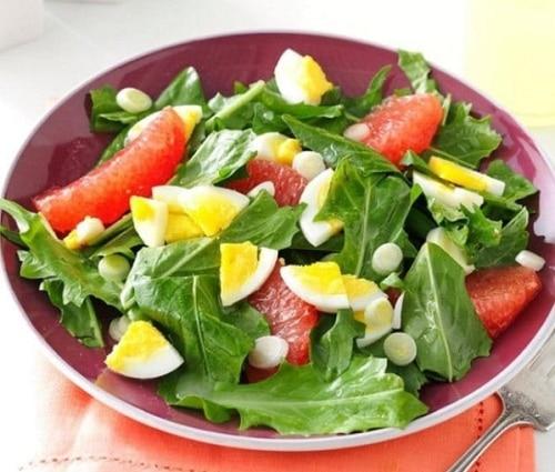 Salát z listů pampelišek s vařeným vejcem a měsíčky grepu.