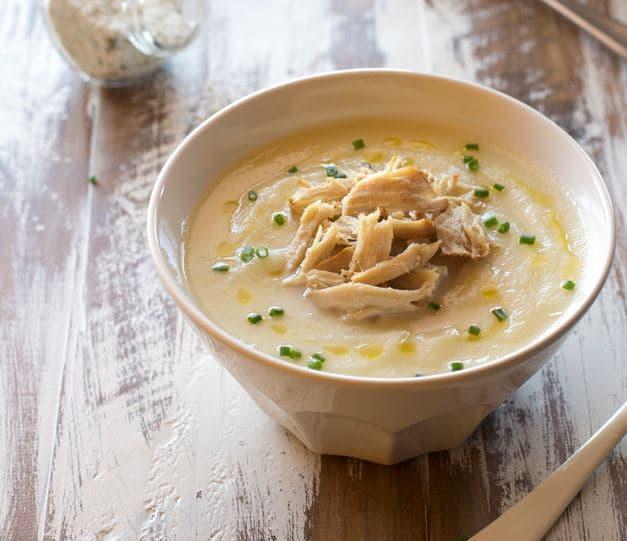 Rozmixovaná květáková polévka s vepřovým masem v bílé misce.