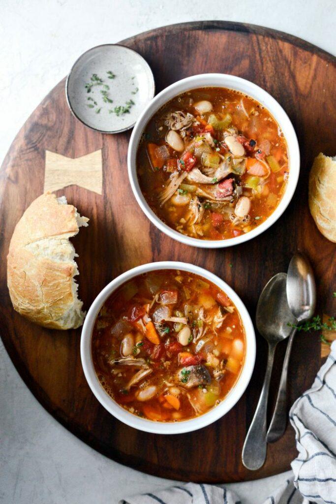 Polévka s fazolemi, zeleninou a vepřovým masem v bílé misce.