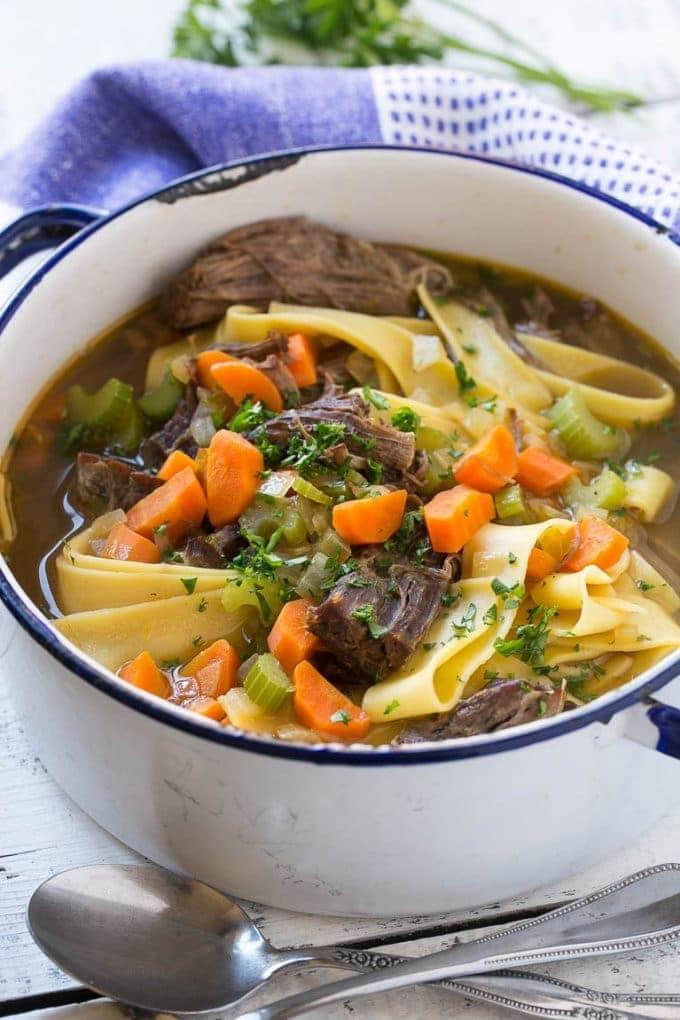 Polévka z hovězího masa z nudlemi a zeleninou v bílé misce.