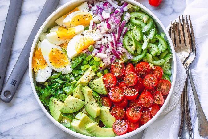 Vejce natrvrdo, avokádo, rajčata, červená cibule, koriandr, jalapoňos a jarní cibulka v hlubokém talíři s vedle položeným příborem.