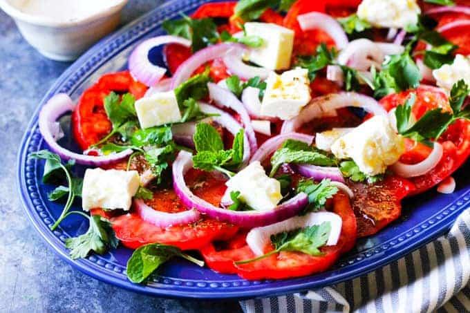 Salát s rajčaty, fetou, červenou cibulí a byinkami na oválném talíři.