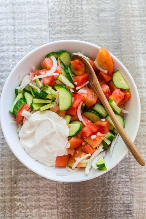 Rajčata, okurky a cibule s majonézovým dresinkem v misce s vařečkou.