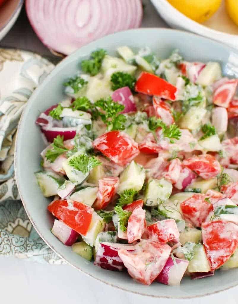 Salát s rajčaty, okurkou, bylinkami a jogurtovým dresinkem v míse.