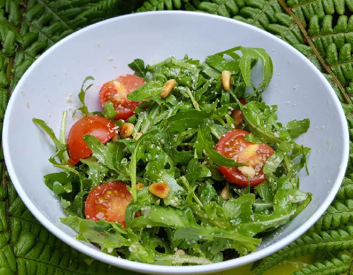 Salát s rukolou, rajčaty a parmezánem servírovaný v míse.