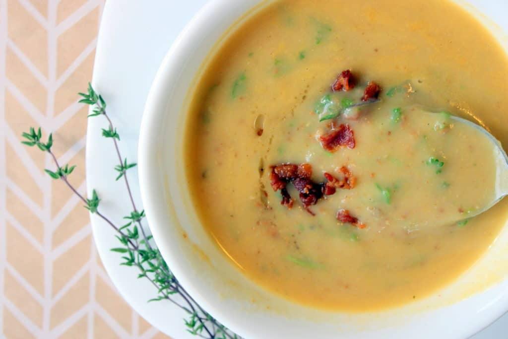 Rozmixovaná polévka z brambor a slaninou v bílém talíři.