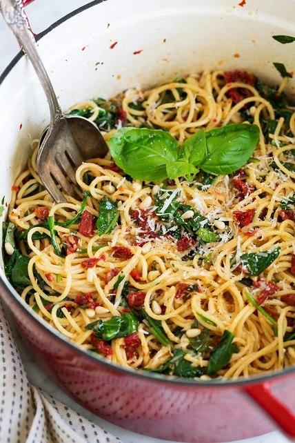 Špagety se sušenými rajčaty, špenátem, oříšky a parmazánem.