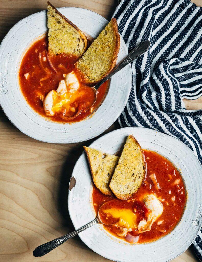 Tomatová polévka s vejcem a chlebem v bílém talíři.