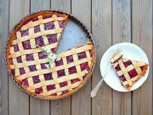 Tvarohový koláč s ovocným džemem pokladený proužky těsta ve formě a vedle položený talířek s porcí koláče a vidličkou.