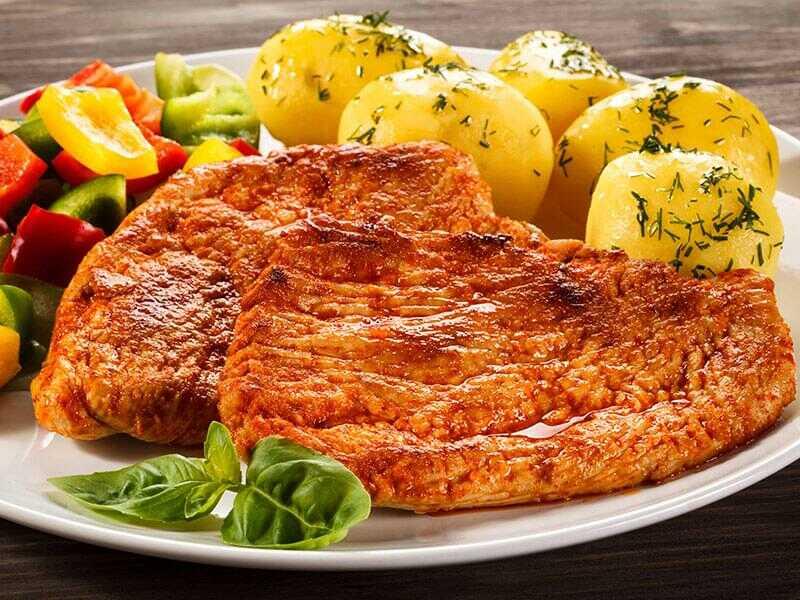 Vepřové plátky s paprikou na talíři s bramborami a zeleninou.