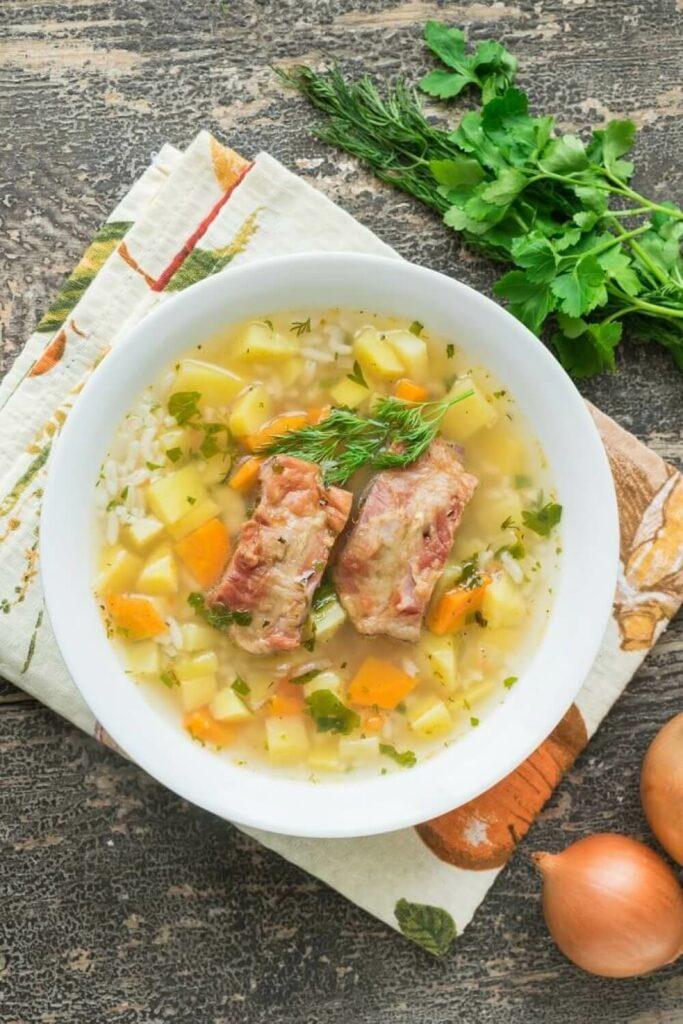 Polévka s uzeným masem, zeleninou rýží a bylinkami.