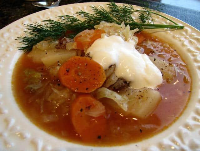 Zelná polévka se zeleninou, hovězím masem a zakysanou smetanou na hlubokém talíři s koprem.
