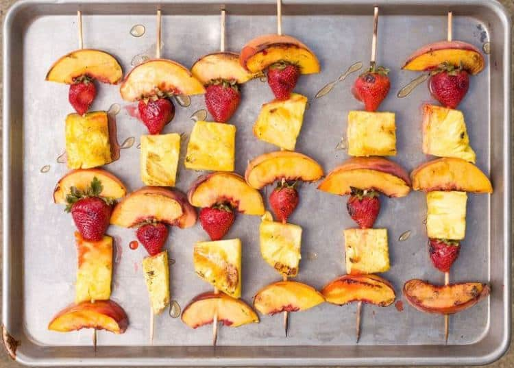 Dezert v podobě grilovaného ananasu jahod a broskví na špejli