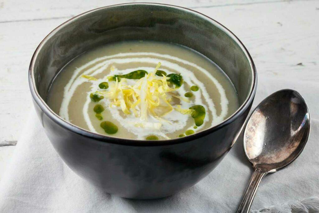 Zeleninová polévka se smetanou v misce se lžící.
