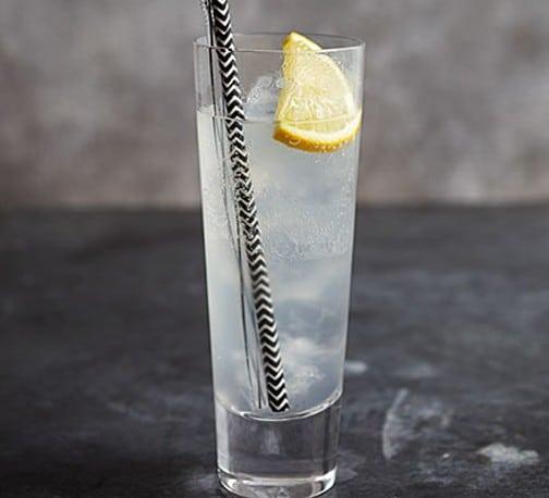 Drink ve sklenici s brčkem a plátkem citronu.