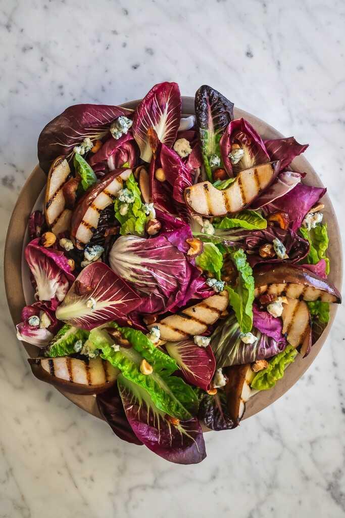 Salát s listovou zeleninou, grilovanou hruškou a dresinkem v míse.
