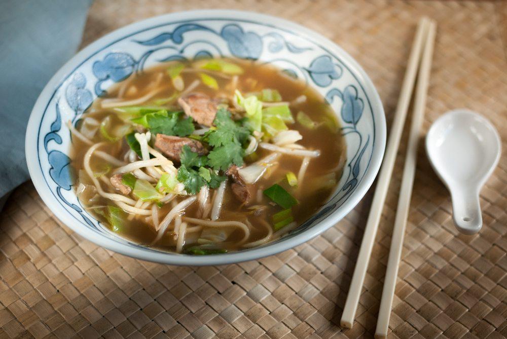 Čínská polévka s masem a nudlemi v misce.