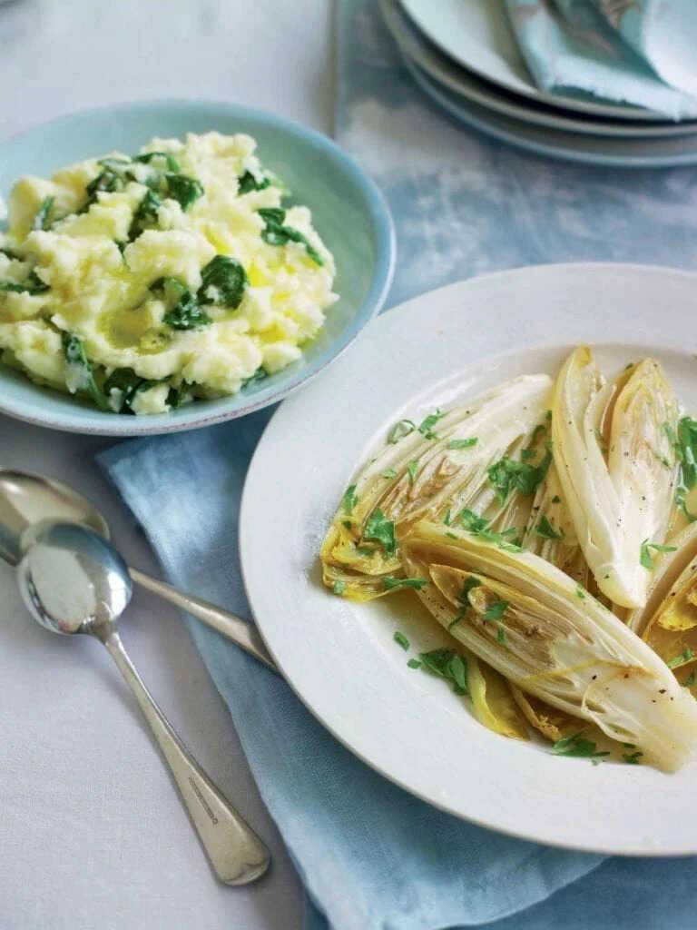 Dušená zelenina na másle na talíři s vedle položenými lžícemi a talířkem se šťouchanými bramborami.
