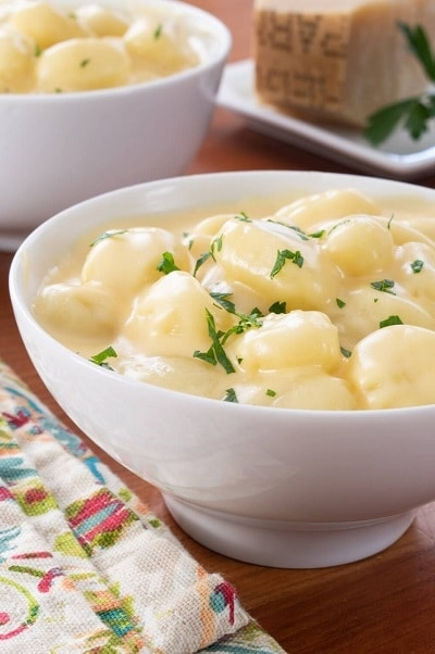 Gnocchi se sýrovou omáčkou, zdobené čerstvými bylinkami.