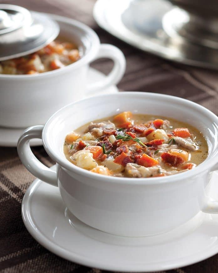 Polévka s masem, slaninou a zeleninou v bílém hrnku.