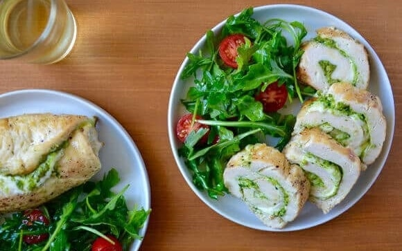 Kuřecí roláda se sýrem a bazalkou, podávaná s čerstvým salátem s rajčaty.