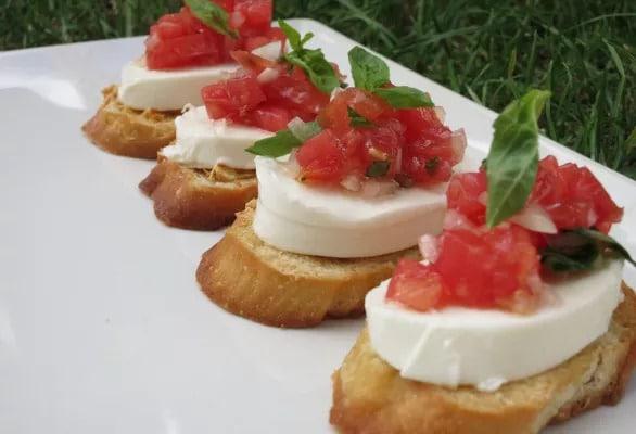 Nakrájená veka s mozarellou a rajčatovou směsí ozdobená bazalkou.