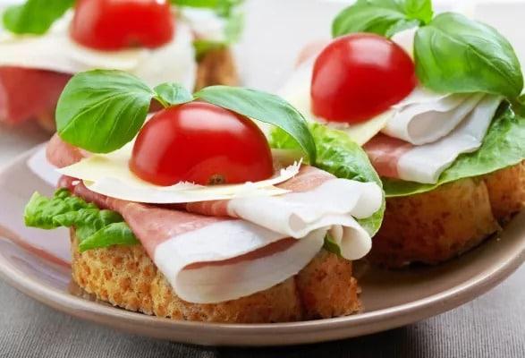 Pečivo se šunkou, sýrem, rajčatem a bazalkou na talíři.