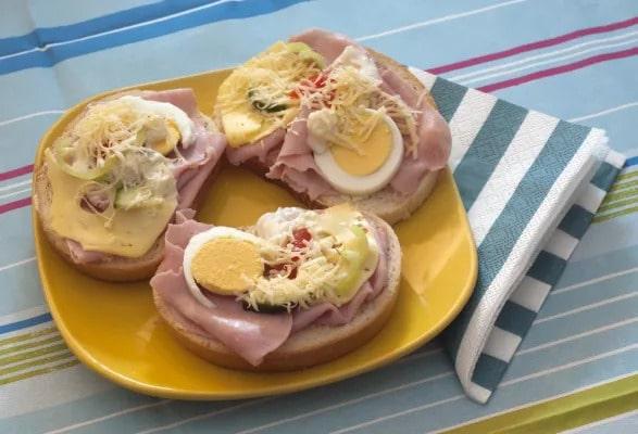 Chlebíčky se šunkou, vajíčkem a zeleninou, posypané sýrem na talíři.