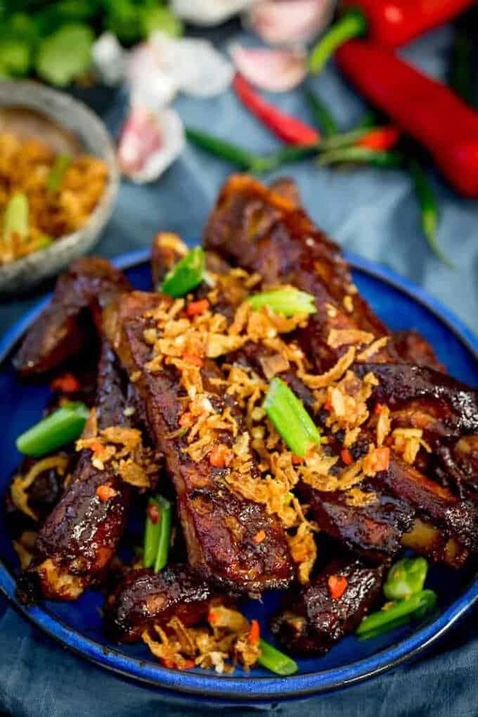 Vepřová žebra posypaná sušenou dibulkou, jarní cibulkou a chilli na talíři.