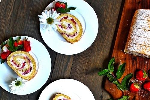 Ovocná roláda, plněná lučinou a plátky jahod, sypaná moučkovým cukrem.