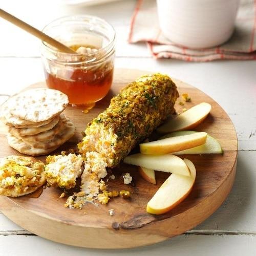 Sýrová roláda, obalená oříšky, podávaná s medem, jablky a krekry.