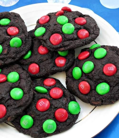 Čokoládové vánoční sušenky ozdobené červenými a zelenými lentilkami.