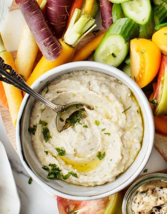 Fazolový dip servírovaný v misce se lžičkou a čerstvou zeleninou.