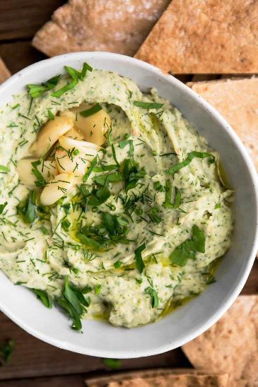 Pomazánka z bílých fazolí s pečeným česnekem servírovaná v misce, zasypaná čerstvými bylinkami.