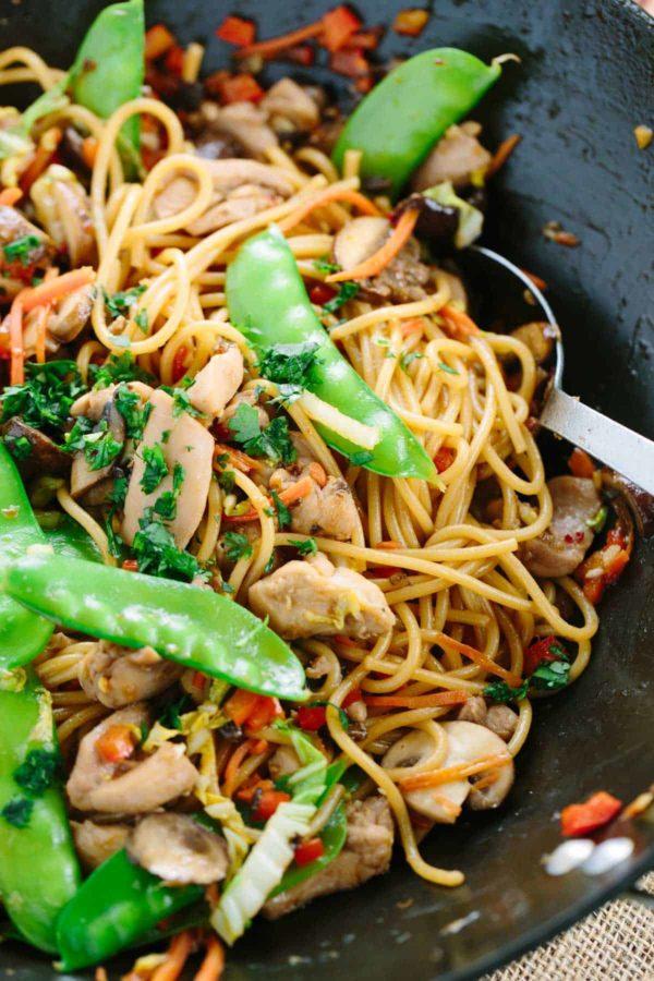 Asijské restované nudle s česnekem, kousky kuřete a čerstvou zeleninou.