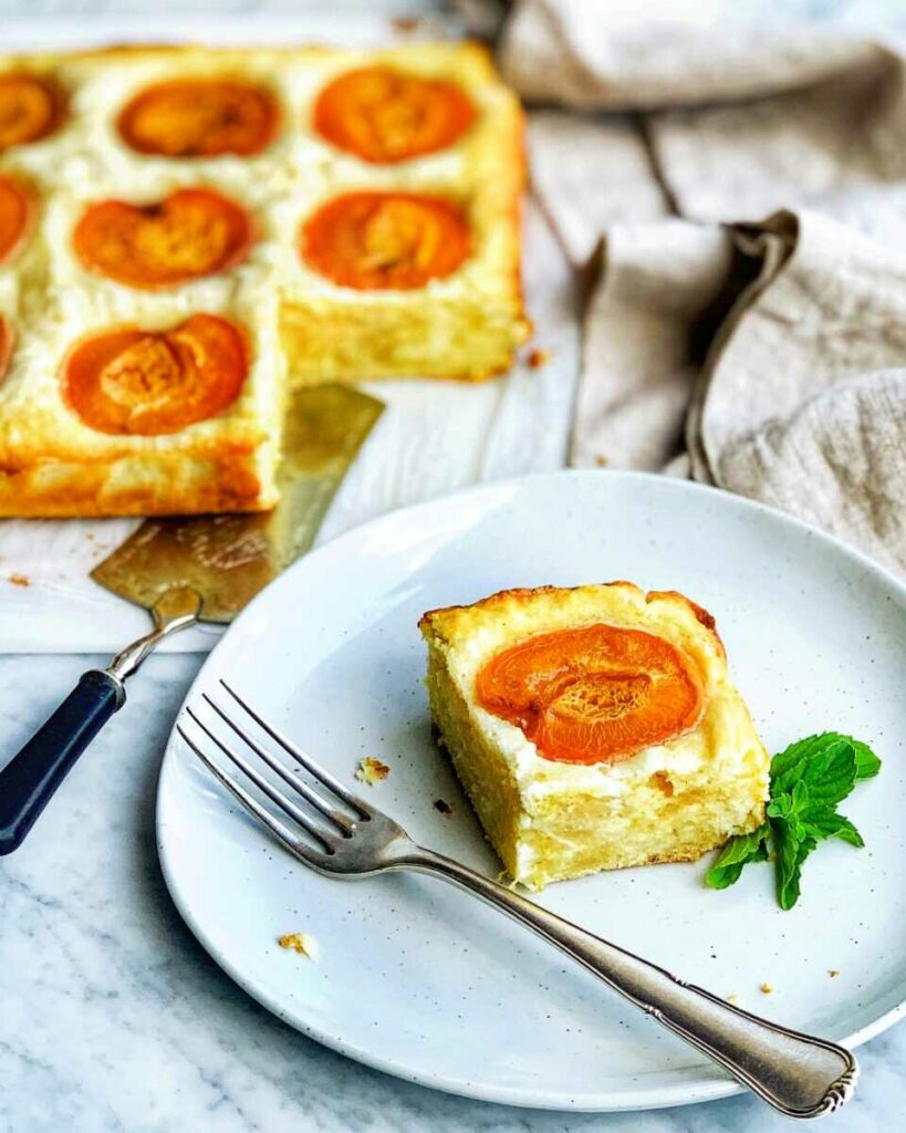 Meruňkový koláč servírovaný na talířku s vidličkou.