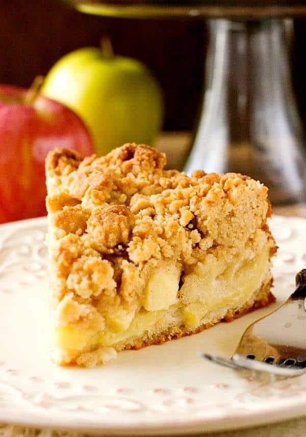 Kousek jablkového koláče s drobenkou servírovaný na talířku s vidličkou.